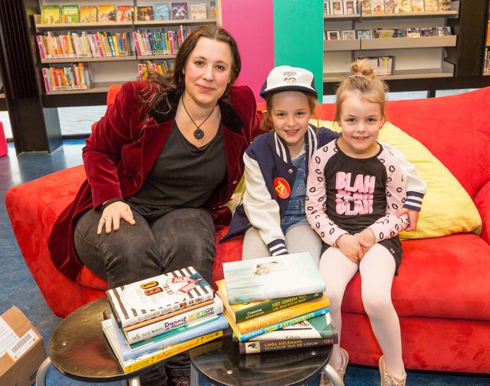 Yfke van Oosten (midden) in de bibliotheek in Heinkenszand met zusje Benthe en kinderboekenschrijfster Sanne Rooseboom.