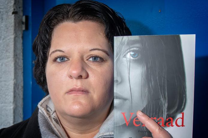 Marion Alblas bij de blauwe deur in De Ridderhof in Alphen, de plek waar de overvallers de winkel betraden en die ook een rol speelt in haar thriller.