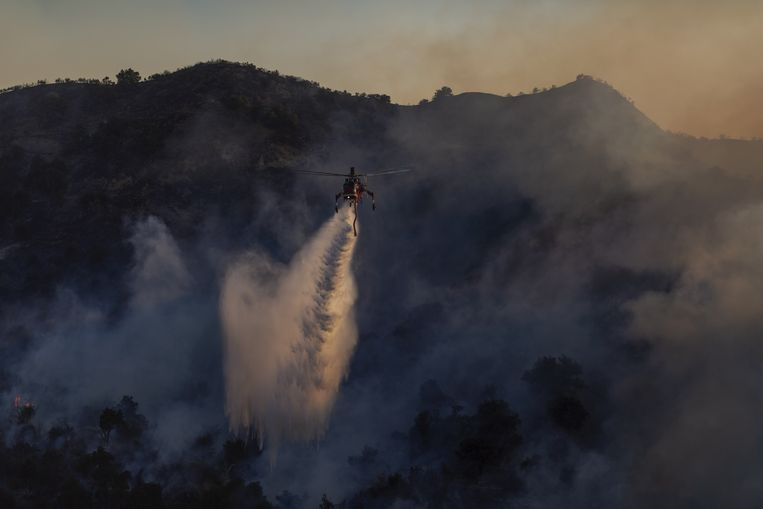 NEWHALL, CA - OCTOBER 11: A firefighting helicopter drops water on the Saddleridge Fire on October 11, 2019 near Newhall, California. The fire has spread to 7500 acres and burned at least two dozen homes   David McNew/Getty Images/AFP == FOR NEWSPAPERS, INTERNET, TELCOS & TELEVISION USE ONLY ==