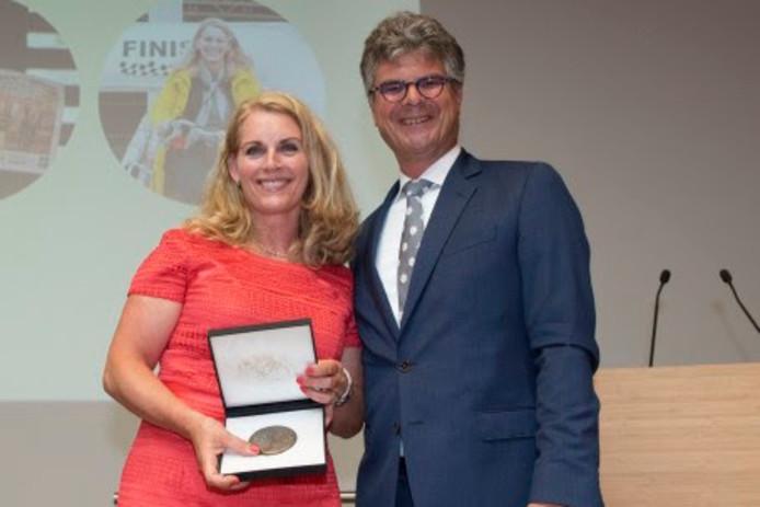 Mariëtte Pennarts ontvangt de erepenning uit handen van de commissaris van de Koning Hans Oosters.