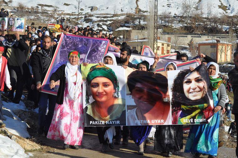 Inwoners van Cizre met portretten van burgers die bij de strijd om het leven zijn gekomen. Beeld afp