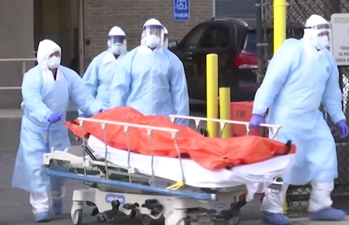 Des infirmiers chargent des corps dans des camions réfrigérés à la vue des automobilistes qui passent.
