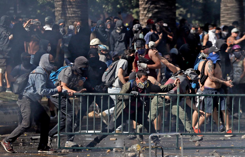 Al dagen zijn er gewelddadigheden in de Chileense binnensteden tussen gemaskerde demonstranten en ordetroepen. Beeld AP