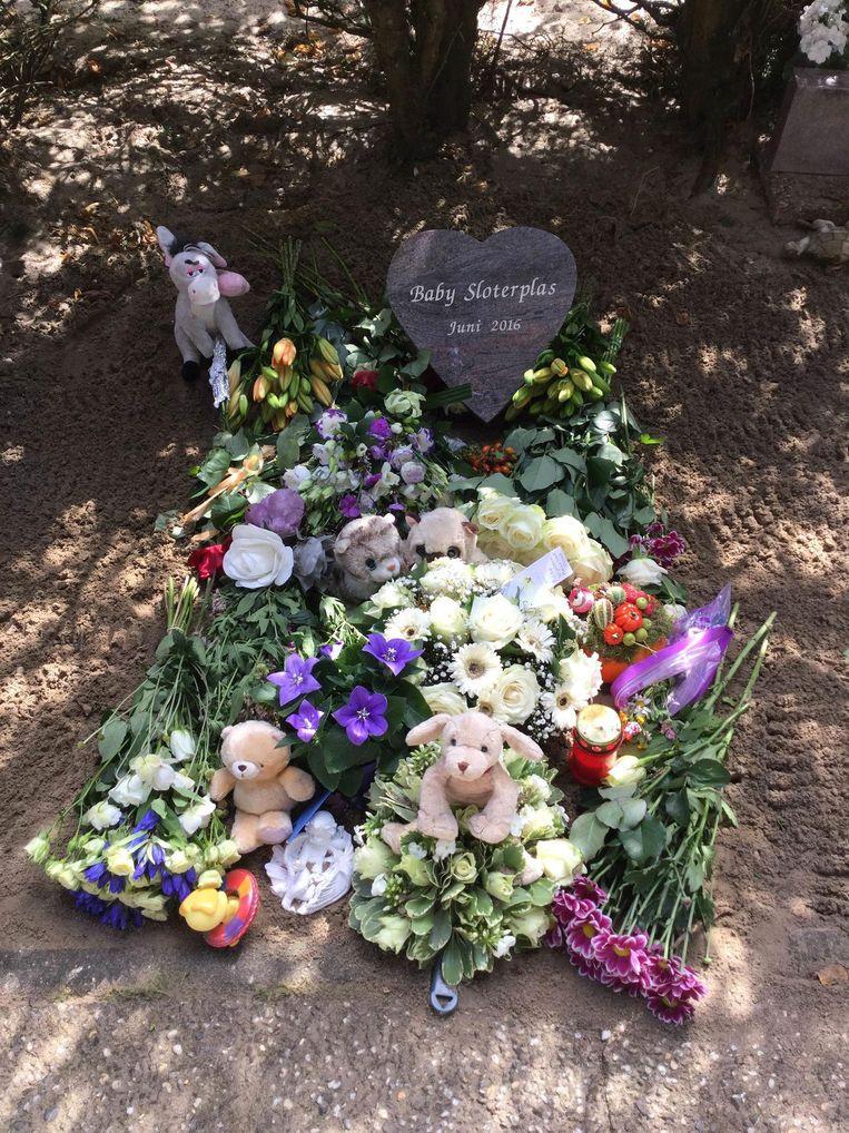 Het grafje dat bedolven is met bloemen, kaarsjes, knuffels, briefjes en gedichten. Beeld Politie