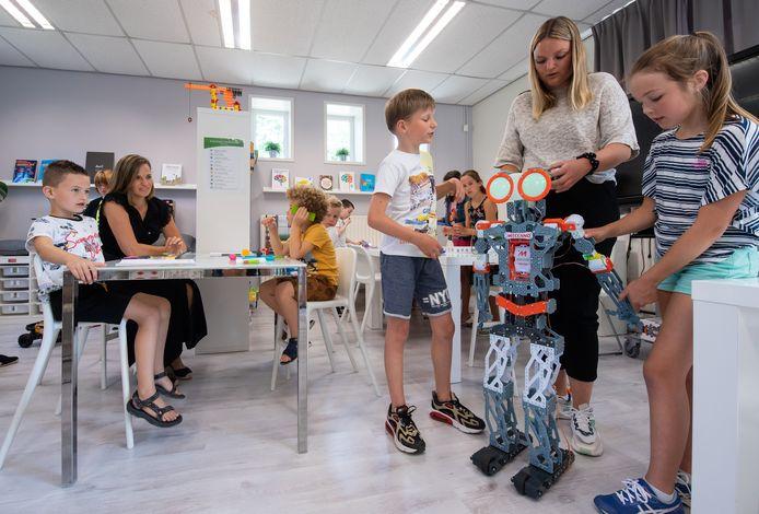 Breda - In de Leerwinkel van basisschool Jacinta in Breda helpen de juffen Lydia Mulders (links aan tafel) en Elisa Wiegerink (rechts achter de robot) leerlingen om extra stapjes te zetten in hun ontwikkeling.