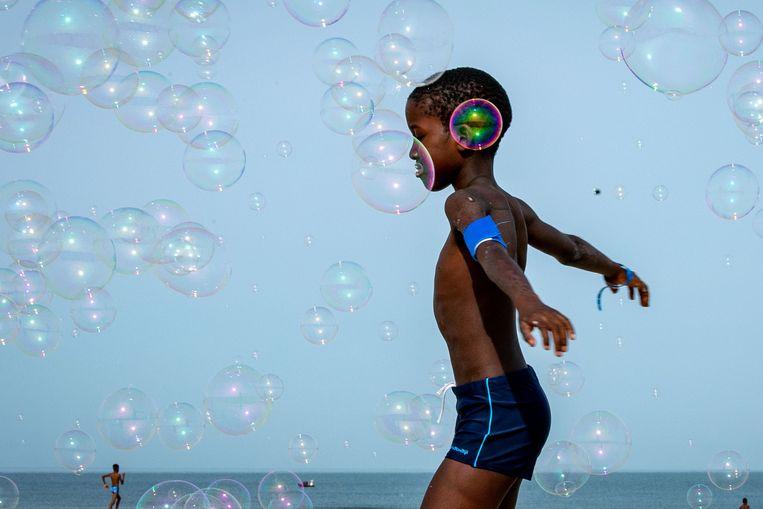 Een jongen speelt met zeepbellen op het strand van het Franse Deauville. Het kind viert vakantie dankzij een stichting  die kinderen uit gezinnen die weinig geld hebben een vakantie aanbiedt.  Beeld AFP