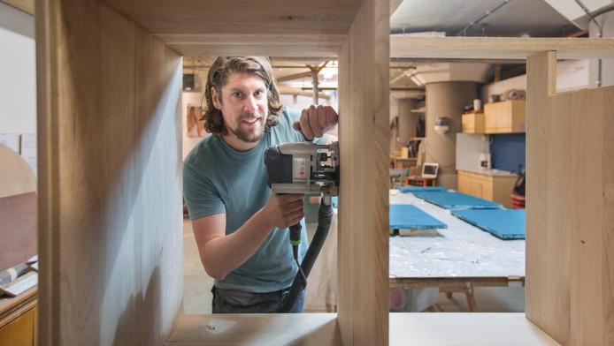 Meubelmaker Niek Hijlkema is in zijn werkplaats bezig aan een nieuw meubelstuk.