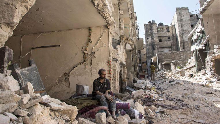 Een Syrische man aanschouwt het puin na de aanslag.