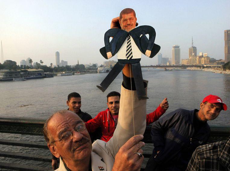 De Egyptische kunstenaar Mohammed Darwish poseert met een trekpop van president Mursi, twee jaar na de val van het bewind van Hosni Mubarak. Beeld ap