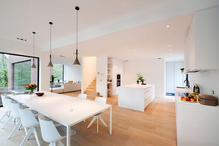 Het interieur baadt in het licht en oogt bijzonder ruim. De witte tinten voor wanden en meubelen overheersen, maar de houten accenten van de trap en de parketvloer geven extra warmte en cachet.