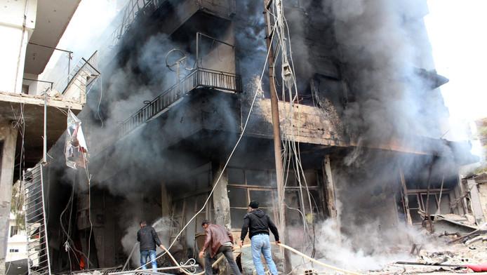 Mannen proberen een brand in een gebouw in Damascus te blussen.