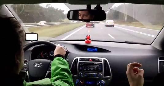 Een screenshot uit een video vanuit de auto die het verkeer op de A59 wil stoppen. Links achter het stuur zit vegan streaker Peter Janssen.