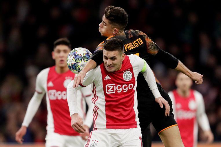 Ajax-aanvaller Tadic met in zijn rug Valencia-verdediger Paulista, die vlak voor tijd een rode kaart kreeg.  Beeld BSR Agency