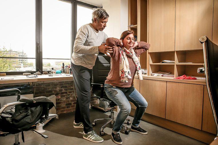 Oefening aan je bureau: Zet je voeten plat op de grond met je tenen mooi recht naar voor. Vouw je handen achter je hoofd, recht je rug, trek je schouders naar achter, sta zo op van je stoel en ga weer zitten