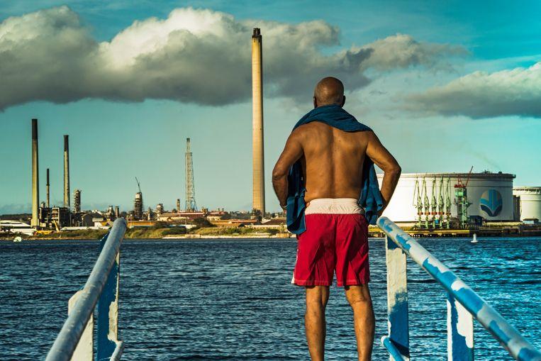 Een man kijkt naar de Isla raffinaderij op Curaçao. Beeld Sinaya Wolfert