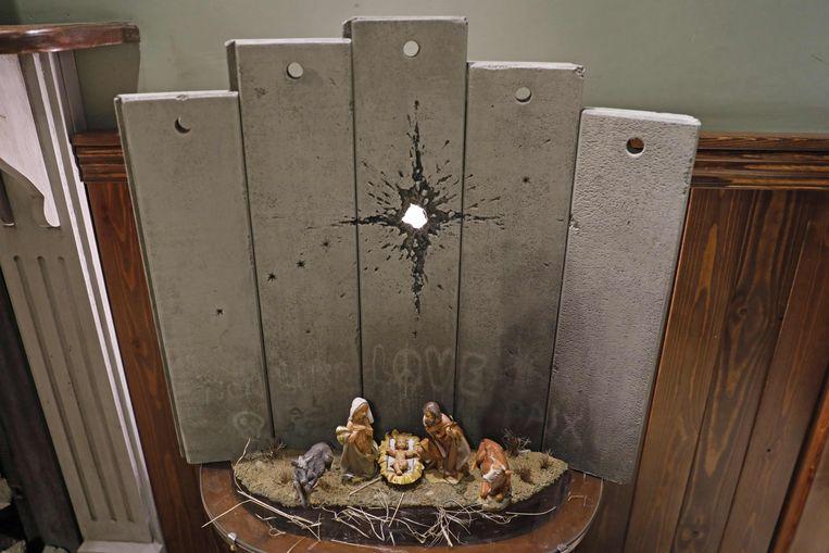 Het kunstwerk genaamd het 'Litteken van Bethlehem' van de straatkunstenaar Banksy in het Walled-Off Hotel in Bethlehem op de Westelijke Jordaanoever. Beeld AFP