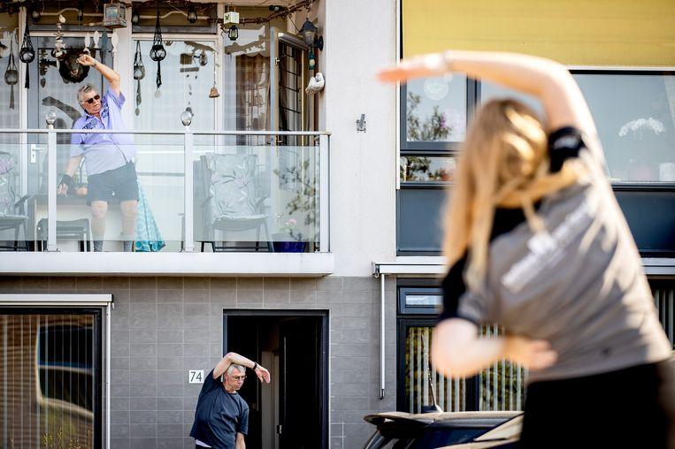 Ouderen volgen gymles vanaf hun balkon in de Kwintsheul.  Beeld ANP