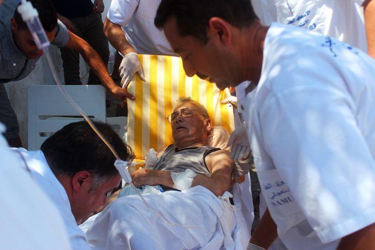 Een gewonde man wordt weggebracht.