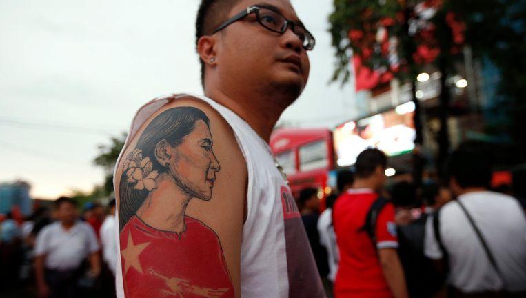Een aanhanger van Aung San Suu Kyi heeft haar portret op zijn arm getatoeëerd. Beeld epa