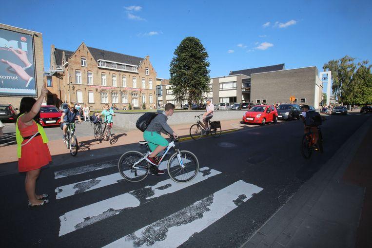 Een gemachtigd opzichter laat de leerlingen, die wél met de fiets durven komen, oversteken aan het MMI.