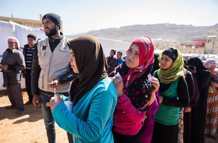 Syrische vluchtelingen nabij de Libanese stad Arsal wachten op voedsel dat wordt uitgedeeld door een NGO. Er zijn inmiddels meer dan 1,1 miljoen Syrische vluchtelingen in Libanon. Beeld afp
