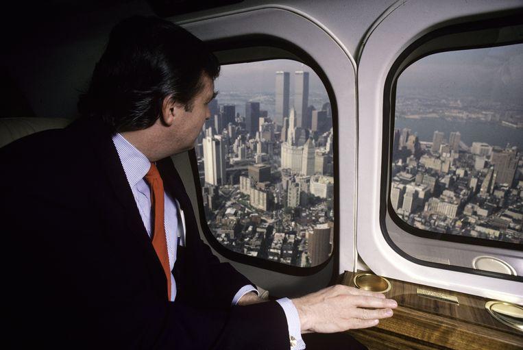 Een jonge Donald Trump kijkt in 1987 vanuit ene helikopter neer op Manhattan. Beeld Getty Images