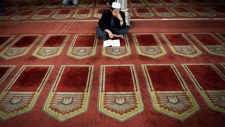 Man leest de Koran in de Al-Azhar moskee in Caïro, 2014. Beeld afp