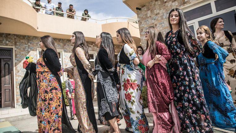 Kinderen en leraressen op een Amerikaanse school in feestelijke kleding, een dag voor het Koerdische referendum. Beeld Marlena Waldthausen