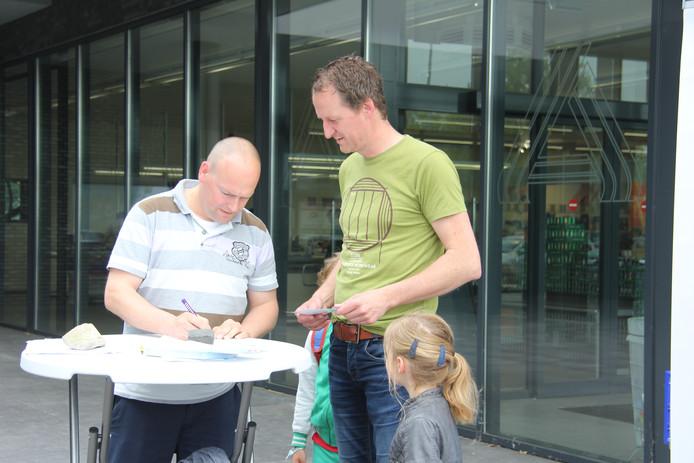 Ferrie Witsiers (links) uit Megen tekent de petitie tegen windmolens.