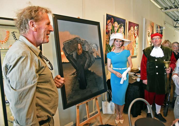 Diva Anouschka Harms, geassisteerd door stadsomroeper Marco van Avermaete (rechts), bij het zojuist in Lokaal 54 in Terneuzen onthulde schilderij van Roeland van der Kley.