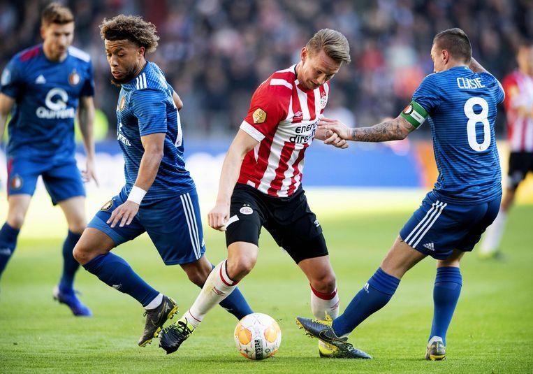 PSV-aanvaller Luuk de Jong (midden) in duel met Jordy Clasie (rechts) en Tonny Vilhena van Feyenoord. Beeld AFP