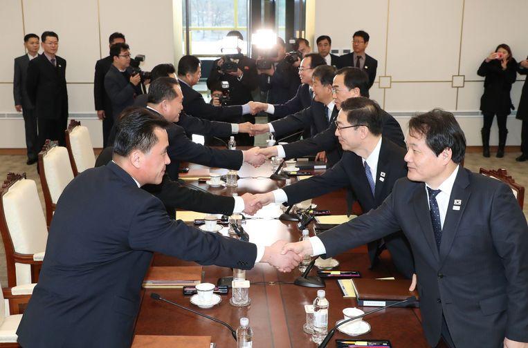 Leden van de Zuid-Koreaanse delegatie (rechts) schudden de hand met leden van de Noord-Koreaanse delegatie (links) tijdens hun meeting in Panmunjeom, in de gedemilitariseerde zone tussen beiden landen.