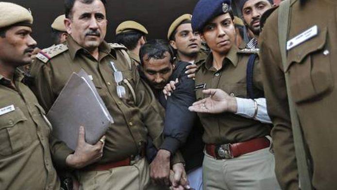 De chauffeur die van verkrachting beschuldigd wordt te midden van politieagenten in de Indiase hoofdstad New Delhi