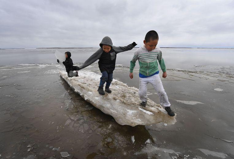 Kinderen spelen op smeltende ijsblokken in een door klimaatverandering getroffen Eskimo dorp in de Yukon Delta in Alaska. Beeld AFP