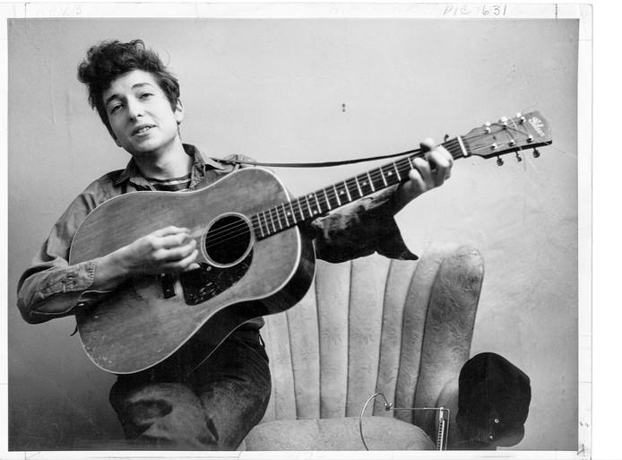 Bob Dylan poseert met zijn Gibson gitaar.