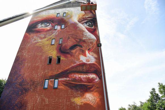 Een monumentaal portret tegen de gevel van het flatgebouw Serbos 3 in de Boonwijk.