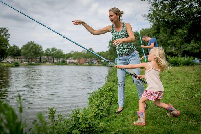 Nim (4) en haar moeder Barbara Freriks beproeven hun geluk in de visvijver aan de Ree rinklanden.
