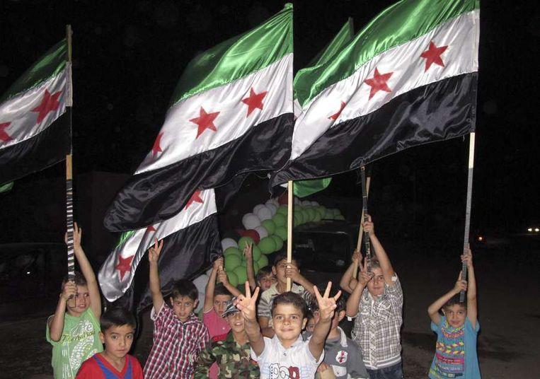 Syrische kinderen zwaaien met de verzetsvlag tijdens een bruiloft tussen drie leden van het Vrije Syrische Leger in Sarmada. Beeld reuters