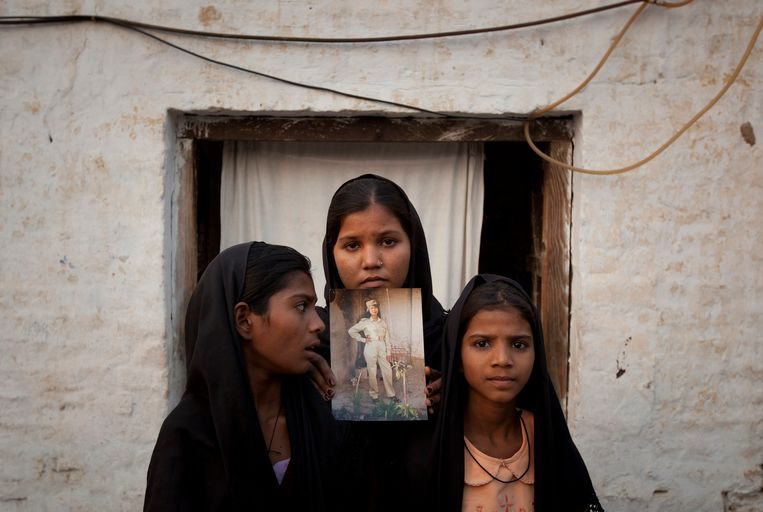 De dochters van Asia Bibi tonen een foto van hun moeder, kort na haar eerste terdoodveroordeling in 2010. Beeld REUTERS
