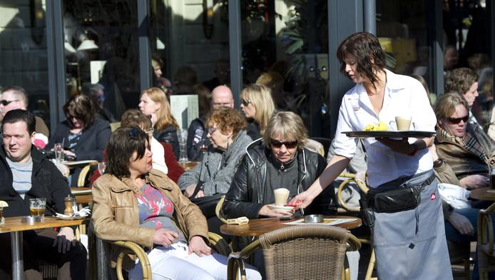 Mensen genieten zondag van de voorjaarszon op het terras op het Rembrandtplein in het centrum van Amsterdam