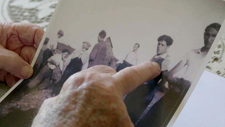 Max Stodel wijst op een foto zichzelf aan in werkkamp Kremboong. Beeld still uit Alles Komt Terug