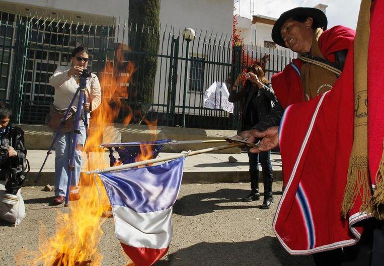 Boliviaanse demonstranten verbrandden Franse en Europese vlaggen voor de Franse ambassade in La Paz. Beeld reuters