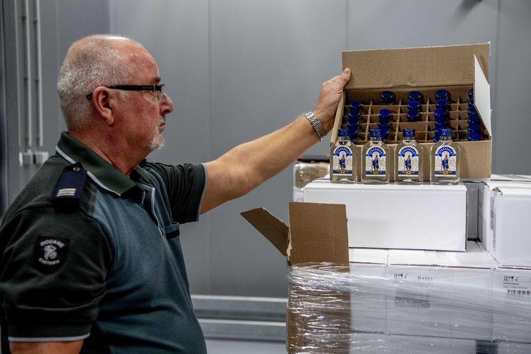 Een Nederlandse douanier bij de in beslag genomen lading. De douane in de Rotterdamse haven onderschepte een container met 90.000 flessen wodka. De lading was mogelijk bestemd voor de Noord-Koreaanse leider Kim Jong-un en zijn legerleiding.