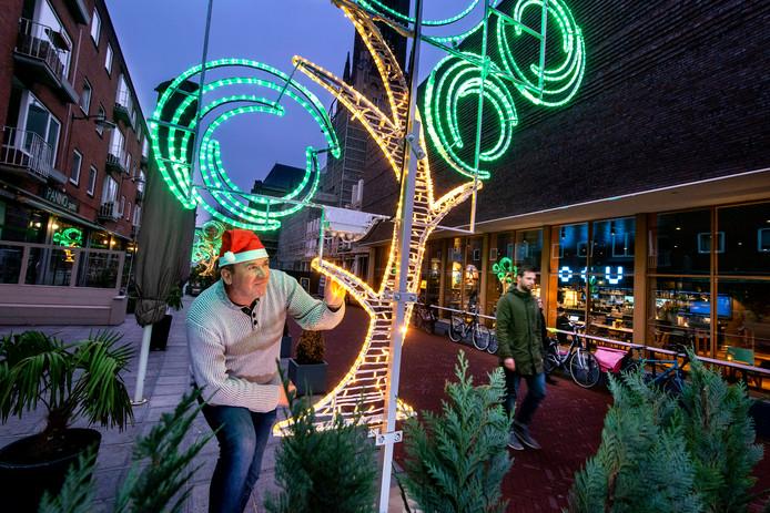 Sander Wind plaatst een van de fonkelnieuwe kerstbomen in het stadscentrum.