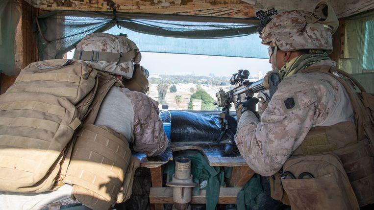Twee soldaten zitten op wacht bij de Amerikaanse ambassade in Bagdad.  Beeld EPA