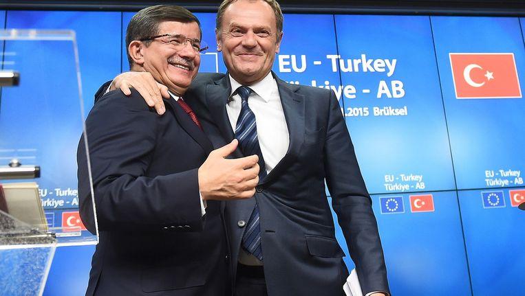 De Turkse premier Ahmet Davotuglu en de president van de EU, Donald Tusk, omarmen elkaar. Beeld afp