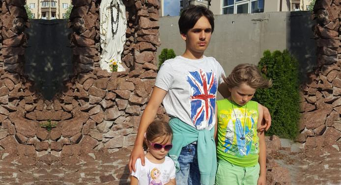 Arina (5), Maksim (14) en Denis (10) op het terrein voor de kerk in Kiev.