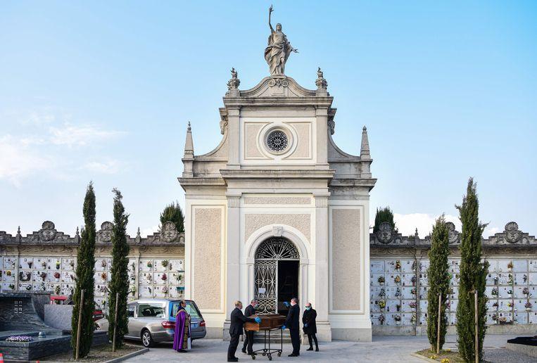 Een begraafplaats in het Italiaanse Bergamo: een man met een gezichtsmasker staat bij een doodskist met daarin zijn moeder die is overleden aan de gevolgen van het coronavirus. Beeld AFP