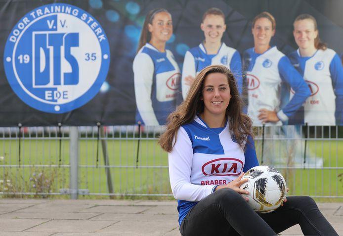 """Joëlle de Bondt poseert voor een grote banner van haar elftal op het sportpark van DTS Ede. ,,Ik sta helemaal links."""""""