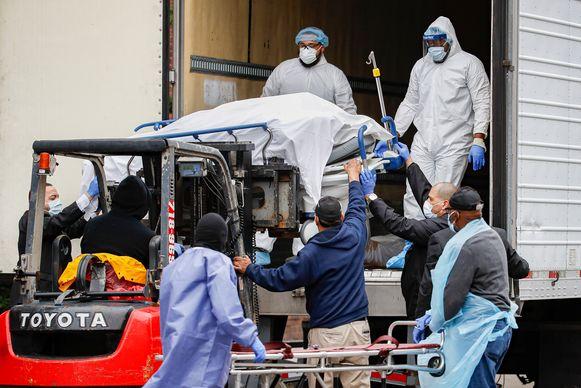 Het lichaam van een overleden coronapatiënt wordt met een vorklift uit een koelvrachtwagen gehaald in Brooklyn, om in een lijkwagen geladen te worden en naar een mortuarium overgebracht.